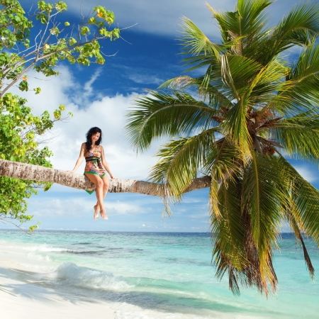 resort life: Fashion woman siting upon palm tree on the beach Stock Photo