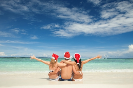 beach happy new year: Happy friends in santa hats on the beach. Christmas vacation