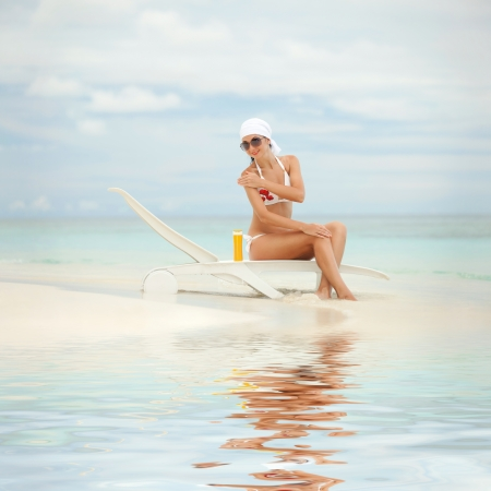 sun lotion: Young woman with sun-protection cream on the beach