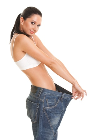 big women: Pretty woman shows her weight loss by wearing an old jeans, isolated on white background Stock Photo