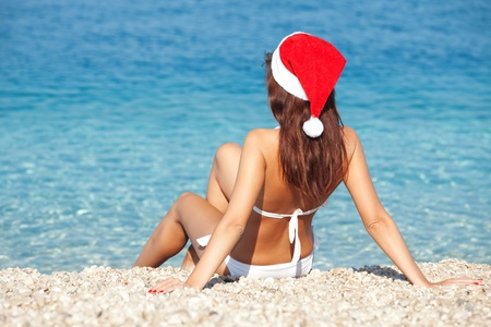 Young woman in santa hat sitting on the beach. Christmas vacation photo