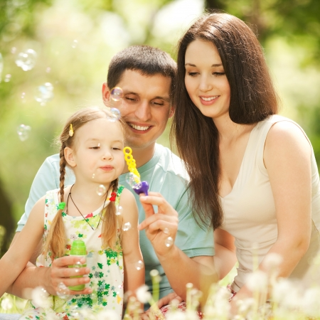 Happy mother, father and daughter blowing bubbles in the park photo