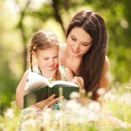 niños leyendo: Madre con la hija en el parque Foto de archivo