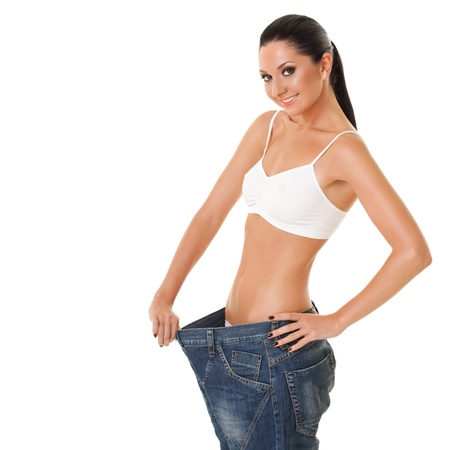 big women: Funny woman shows her weight loss by wearing an old jeans, isolated on white background Stock Photo