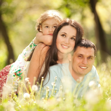 healthy people: Happy mother, father and daughter in the park