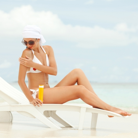 solarium: Young woman with sun-protection cream on the beach