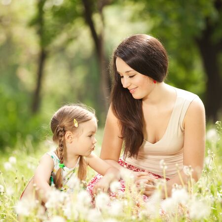 Mother communicate with daughter in the park photo