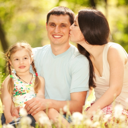 Happy mother, father and daughter in the park photo