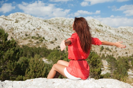 Beautiful woman sitting before the mountains. Lifes enjoyment Imagens