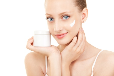 woman face cream: Cute woman applying cream to her face
