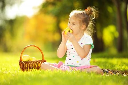 little girl eating: Cute little girl eating apple in the park