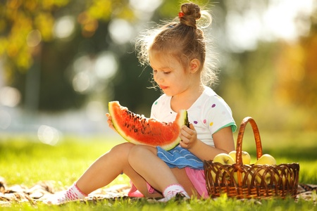 Cute little girl eating watermelon photo