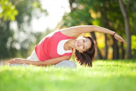 pilate: Jolie femme faisant des exercices de yoga dans le parc Banque d'images