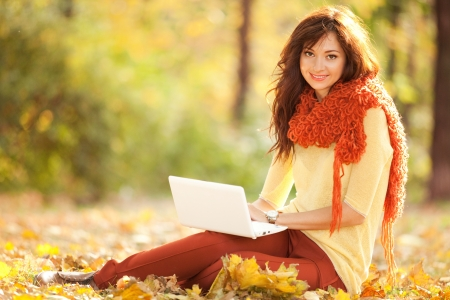 Cute woman with white laptop in the autumn park Stock Photo - 16334080