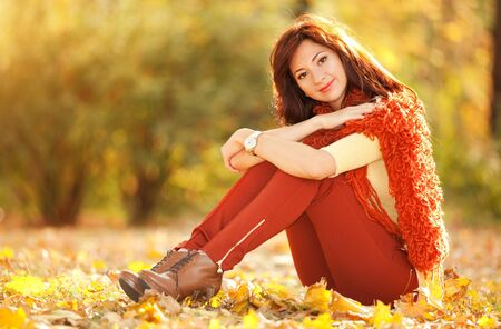 Young pretty woman resting in the autumn park photo