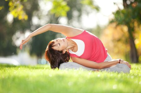 yoga pose: Pretty woman doing yoga exercises in the park