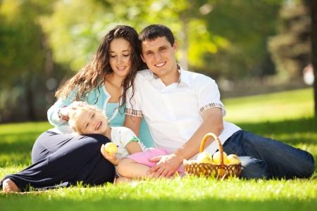 padres e hijos felices: Familia feliz con un picnic en el jardín verde