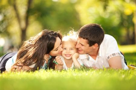 家庭: 快樂的父親和母親親吻自己的女兒在公園裡 版權商用圖片