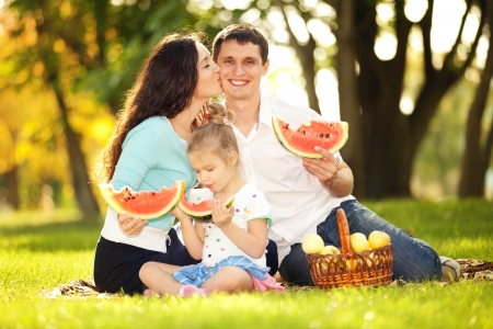 Happy family having a picnic in the green garden Stock Photo - 16406217