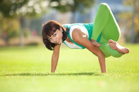 Pretty woman doing yoga exercises in the park photo