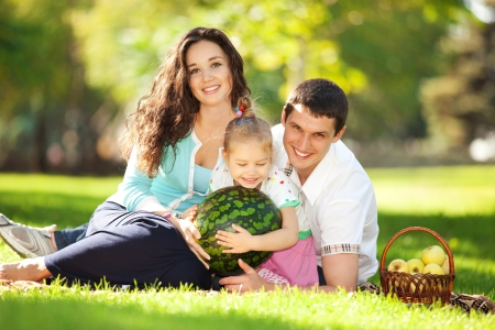 family garden: Happy family having a picnic in the green garden