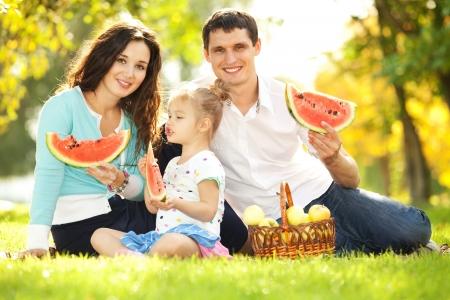 frutas divertidas: Familia feliz con un picnic en el jard�n verde