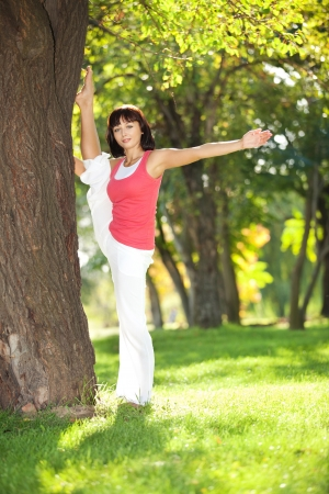 Pretty woman doing sports exercises in the park photo