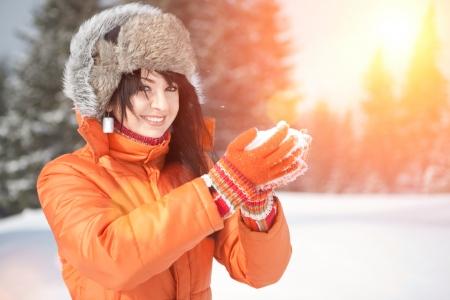 Happy girl jouer avec la neige dans le paysage d'hiver