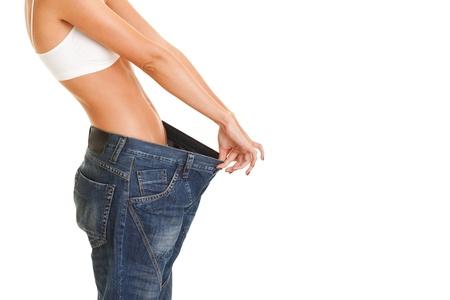 mujer muestra su pérdida de peso usando un jeans viejos, aislados en fondo blanco