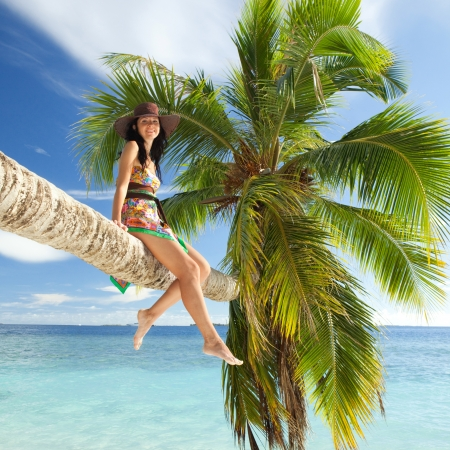Fashion woman siting upon palm tree on the beach Stock Photo