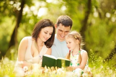 Heureuse mère, le père et sa fille de lire un livre dans le parc Banque d'images