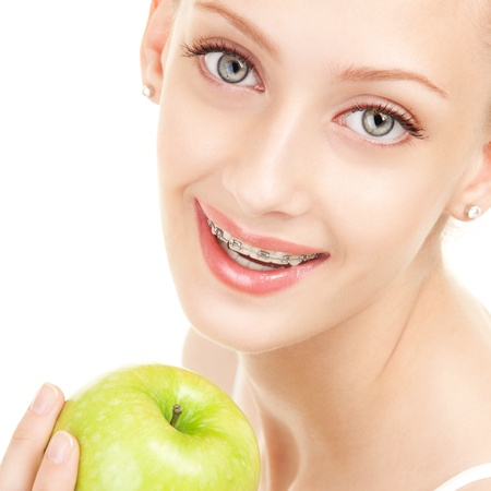 Cute girl in braces with green apple on white background Stock Photo - 16690845