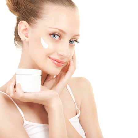 face cream: Cute woman applying cream to her face