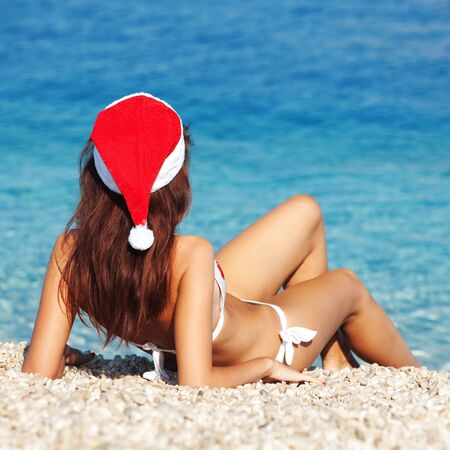 Young woman in santa hat sitting on the beach  Christmas vacation photo