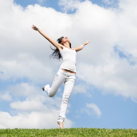 Hübsche junge Frau springt auf grünem Gras Standard-Bild