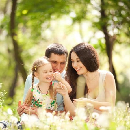 familie: Gelukkige moeder, vader en dochter spelen in het park