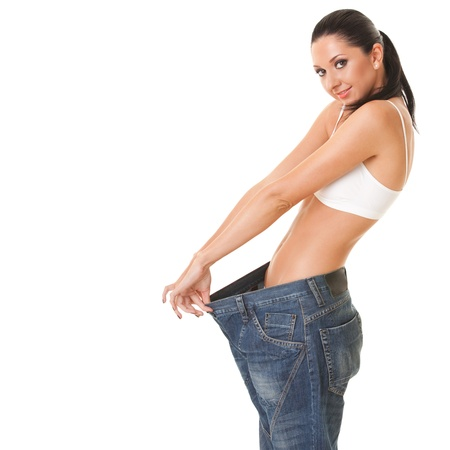 Pretty woman shows her weight loss by wearing an old jeans, isolated on white background Stock Photo