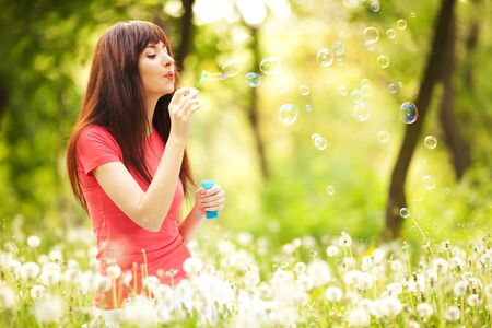 Happy woman blowing bubbles in the park photo