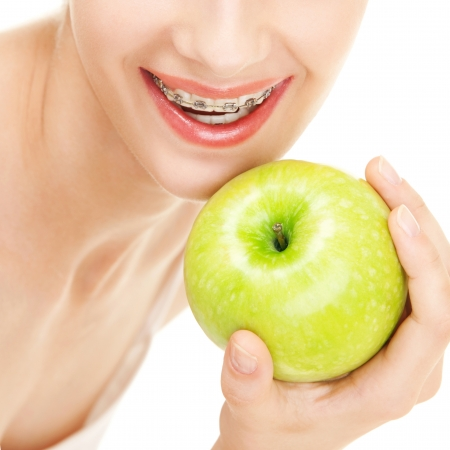 Girl in braces with green apple on white background photo