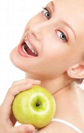 Cute girl dans des accolades à la pomme verte sur fond blanc