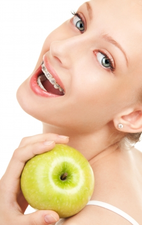 Cute girl in braces with green apple on white background photo