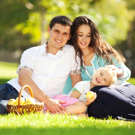 Happy family having a picnic in the green garden photo