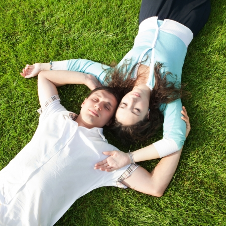 sun down: Happy couple relaxing on green grass