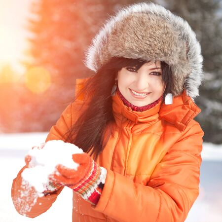 Happy girl playing with snow in the winter landscape photo