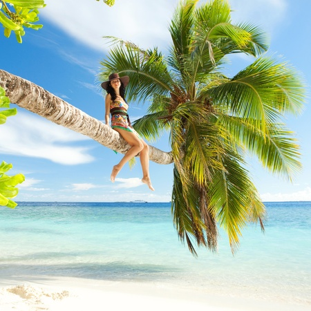 bliss: Fashion woman siting upon palm tree on the beach Stock Photo