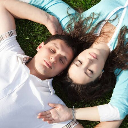 Happy couple relaxing on green grass Stock Photo - 16904280
