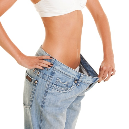 slender: woman shows her weight loss by wearing an old jeans, isolated on white background