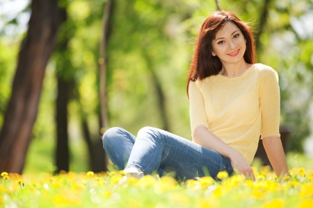 Young happy woman in the park with flowers photo