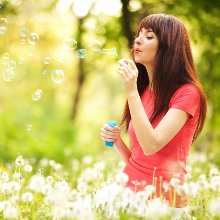 blowing dandelion: Happy woman blowing bubbles in the park Stock Photo