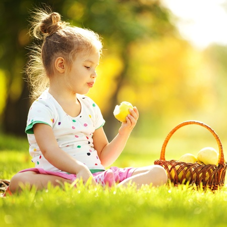 Cute little girl eating apple in the park photo